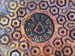 Bell System manhole design (Zombie37) Tags: street old red brown texture industry geometric beautiful yellow contrast vintage found design words 3d rust colorful iron pattern bell geometry painted letters shapes angles rusty gear surface baltimore ring sidewalk cover american round infrastructure castiron lettering manhole hexagons dots circular interlocking raised bellsystem inustrial hexnut