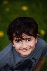 a smile (arrowlili) Tags: flowers boy portrait smile grass canon bokeh canon85mm12