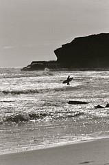 #022137 - done for the day, santa cruz, march 2012. (Jeff Merlet Photography) Tags: ocean california leica bw cliff usa santacruz man film beach silhouette rock 35mm sand published surf pacific kodak tmax surfer wave 400 surfboard 135 37 tmax400 elmar negatif shorebreak 1354 leicam6ttl 201203 elmar135 thelanetowaddell jeffmerletphotography jeffmerlet photojeffmerletcom gamma0555 r0221 022137