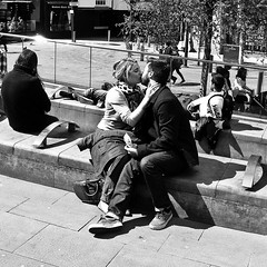 P5121324May 12, 2012-1-2 Inbetween Cadbury's cream eggs... (Lawrence Holmes.) Tags: street uk white black manchester photography mono triangle kiss couple lancashire precinct olympusc7070wz candidandstreet