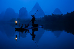 Fisherman on the Li River (Greg Annandale) Tags: china morning travel blue fish water silhouette night forest sunrise canon river dark landscape dawn liriver li boat early fisherman ancient mood guilin yangshuo atmosphere bank bamboo limestone cormorant raft bluehour karst lijiang yangshou guangxi thebluehour karsts lijiangriver canon5dmkii canon5dmk2