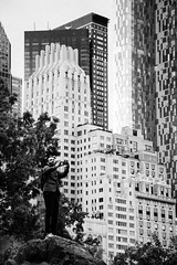Small Man takes Photo in front of Big Buildings (GrandWaz) Tags: photographer street newyork park rock bw 50club