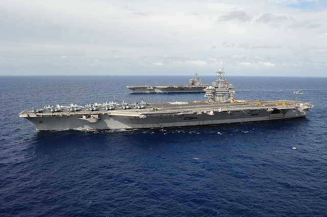 USS Dwight D. Eisenhower participates in an ammunition on-load with USS George H. W. Bush.