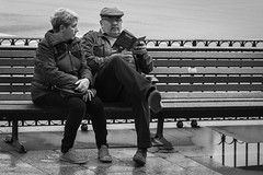 Off to Sunny Spain (rafa_luque) Tags: madrid street bw reflection tourism water rain bench spain sitting candid centro tourists tired unhappy disappointment guidebook cibeles 2012 canoneos550d