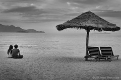 Lovers on Nha Trang Beach (Joss Bomal) Tags: travel sunset sea people blackandwhite love beach photography photo sand holidays asia calm vietnam parasol zen rest lover farniente nhatrang beachumbrella plalmtree