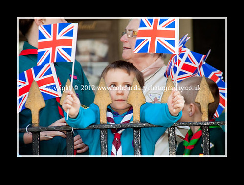A young local resident with flags at the ready waits to meet Her Majesty The Queen-34