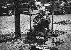 Street Music (pooshda) Tags: bw music playing holland monochrome zeiss blackwhite downtown singing guitar michigan sony streetphotography monochromatic sharp 55mm tuliptime alpha streetmusic cowboyhat harmonica streetperformance 8thstreet a7rii