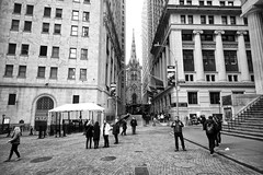 trinity church from wall street, manhattan, new york (twurdemann) Tags: city newyorkcity people urban blackandwhite newyork building tower church parish architecture buildings manhattan crowd streetphotography tourists spire financialdistrict trinitychurch wallstreet capitalism episcopal lowermanhattan banks nyse broadstreet newyorkstockexchange diocese nationalhistoriclandmark pavingbricks niksilverefex xf14mm fujixt1 2016tripnewyork naussastreet