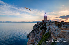 Flying by (Kordelakos) Tags: travel sunset lighthouse nature horizontal architecture landscape outdoors photography afternoon seagull tranquility nobody nopeople romance cliffs illuminated direction dramaticsky protection tranquilscene colorimage horizonoverwater builtstructure