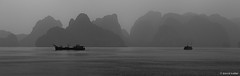 Giants Watching (davidkoiter) Tags: travel bw panorama white black water silhouette canon eos bay boat haze stitch pano wide calm vietnam 7d l series photomerge 70200 f4 halong 2012 f4l aspectratio koiter davidkoiter