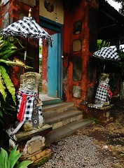 entrance to a palace (SM Tham) Tags: bali plants indonesia island asia doors steps entrance royal statues palace doorway umbrellas gravel parasols guardians karangasem amlapura sashes pedestals chequeredcloth puriagungkarangasem