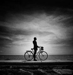 Girl on a bike (Fernando Cabalo) Tags: portrait people blackandwhite bw woman white black love blancoynegro blanco beach girl silhouette clouds portraits contraluz landscape solitude noir mood alone chica shadows retrato negro bicicleta playa bn nubes lonely soledad muralla castellón benicasim miradafavorita ipad2