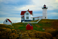 Nubble Lighthouse with Spring Daffodils (SunnyDazzled) Tags: light red lighthouse white house history station island coast spring marine stones shed maine coastal oil cape daffodils neddick nubble