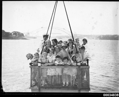 A group of children hoisted by a crane on board HMAS AUSTRALIA II