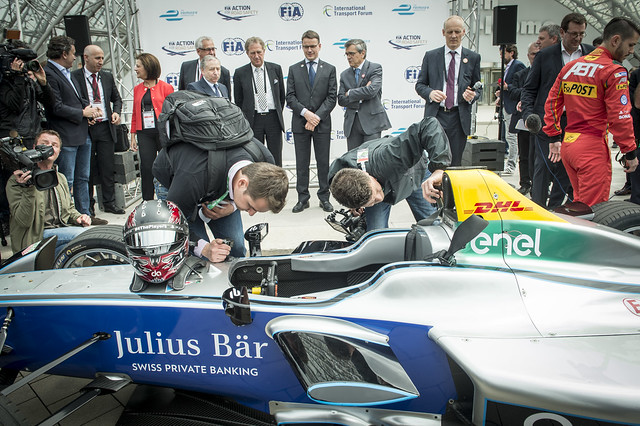 Two Formula E workers prepare the car