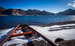 Lake Chzenji Rails (ErikFromCanada) Tags: travel blue winter red sky cloud mountain lake snow mountains cold rock japan stone landscape japanese cool rocks waves waterfront stones tracks rocky rail wideangle calm hike ridge rails nikko ultrawide snowcovered redrails a7r