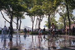 bicycling through the battery park fountain / chinon bellami (ho_hokus) Tags: nyc newyorkcity summer newyork fountain bicycle unitedstates manhattan batterypark 35mmfilm 2012 chinonbellami fujisuperia fujisuperiaxtra400 fujixtra400
