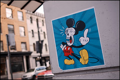 Angry Mickey! (Eric Flexyourhead) Tags: street city blue red urban canada detail art yellow vancouver poster bc bokeh britishcolumbia mickey angry mickeymouse colourful gastown numb powellstreet fragment pissedoff flippingthebird olympusep1 panaleica25mmf14 leicadgsummilux25mmf14asph