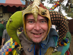 Grinning Jester at the Renaissance Faire (Robb Wilson) Tags: videoframe renaissance irwindale renaissancefaire 2016renaissancepleasurefaire jester clown courtjester conicalbellhat freephotos