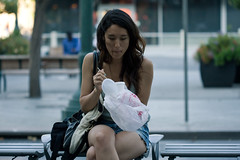Jocelyn eating food. (vilyviane) Tags: portrait food woman face yummy waiting downtown sitting eating candid longhair takeout