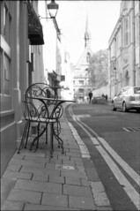 News Cafe, Oxford with Exeter College Tower in Background (David Stumpp |[o]| Photography) Tags: street uk travel light england news college home zeiss photoshop table 50mm daylight cafe chair university day natural asahi kodak scanner united kingdom delta 11 jena exeter f oxford carl epson spotmatic 100 f18 50 developed ilford 1850 xtol cs3 v500 pancolar