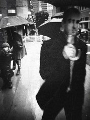 oh i do believe i spot the morton salt lady! (pimpdisclosure) Tags: sf sanfrancisco street city urban blackandwhite bw texture wet rain umbrella stare pimp umbrellas pimpexposure part74 thepimpchronicles pimpdisclosure didyounoticetheguysawesomeheadshotintherightsidebehindtheguyintheblacksuit isilhouettedthepartofthewomanintheshadowunderherumbrellaonpurpose