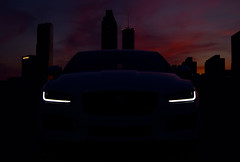In the Concrete Jungle, A Feline Lurks (Stephen Guilbert) Tags: auto city light sunset sky building cars car silhouette skyline night buildings dark lights twilight nikon automobile cityscape dusk headlights jag jaguar automobiles xe carshots