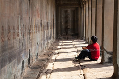 A male traveler sitting alone in the Angkor Wat Corridor (baddoguy) Tags: shadow red people sculpture abstract horizontal photography cambodia sitting loneliness dress adult fulllength tshirt angkorwat tourist unescoworldheritagesite pointofview stonewall copyspace relaxation siemreap angkor awe adultsonly oneperson concepts casualclothing traveldestinations colorimage diminishingperspective famousplace architecturalcolumn onemanonly lightnaturalphenomenon carvingcraftactivity