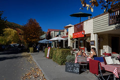 Enjoying Their Coffee (Jocey K) Tags: street autumn trees newzealand sky people signs architecture umbrella buildings pub shadows chairs autumncolours tables shops southisland centralotago cafes arrowtown tripdownsouth