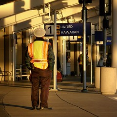 secure, Terminal 1, Oakland International Airport, December 27, 2008 (2) (/\/\ichael Patric|{) Tags: california city morning urban man building sign northerncalifornia yellow architecture sunrise geotagged dawn oakland 1 golden back airport oak december aviation united pickup security terminal sidewalk transportation sanfranciscobayarea hawaiian bayarea eastbay sfbayarea vest 2008 job westcoast curb departures employee alamedacounty arrivals unitedairlines airtravel dropoff terminal1 masstransportation curbside oaklandcalifornia oaklandairport hawaiianairlines commercialaviation michaelpatrick oaklandinternationalairport december2008 alamedacountycalifornia address:continent=northamerica address:country=unitedstatesofamerica address:state=california address:city=oakland address:postalcode=94621 address:street=airportdrive geo:lat=377125 geo:lon=1222132