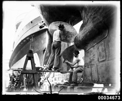 Two sailors cleaning a propeller of the French warship BELLATRIX, 1930-1932