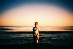 Golden boy (fotobes) Tags: ocean boy sea water sussex lca xpro brighton crossprocess hove horizon grain paddle wave ripples spencer vignetting vignette goldenhour fujivelvia100 laddling