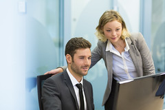 Two business people in a office, working on computer (reputationtempe) Tags: portrait people woman white man male businessman female training work computer happy person corporate office team adult background group working young handsome meeting professional communication business company busy together startup worker colleagues discussion talking manager firm partnership leadership cooperation teamwork caucasian businesspeople businesswoman coworking