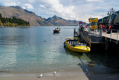 autumn trees newzealand people seagulls lake beach water birds clouds boats shadows hills southisland centralotago queenstown mountians lakewakatipu jetboats