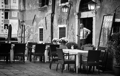 The Bar Owner (Just Ard) Tags: street venice people blackandwhite bw italy white man black blancoynegro monochrome face bar table person photography mono glasses chair nikon eyecontact noiretblanc zwartwit candid 85mm smoking d750 unposed spectacles  biancoenero schwarzundweis justard