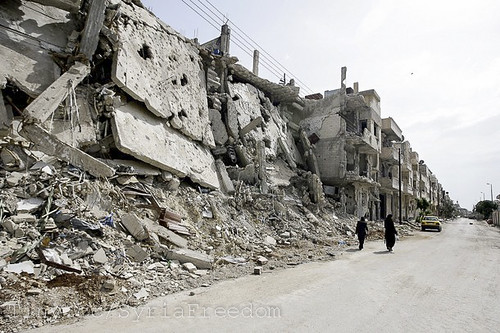 Syrian women walk past destruction of their homesland