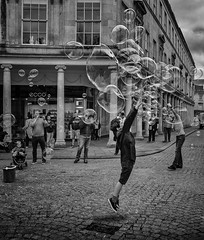 reaching for bubbles (Daz Smith) Tags: city uk boy portrait people urban blackandwhite bw streets blancoynegro monochrome canon blackwhite jumping bath candid citylife thecity streetphotography bubbles canon6d dazsmith
