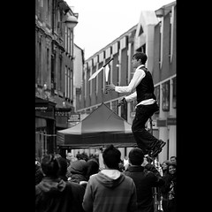 Things you shouldn't do while riding an 8' unicycle (PhotoJunket) Tags: cambridge bw unicycle streetperformer knives juggle juggler marketsquare sigma105mm