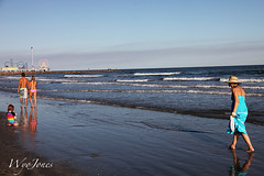 Along the Beach (wyojones) Tags: carnival boy woman usa galveston reflection cute beach gulfofmexico water girl beautiful beauty hat pier sand couple pretty waves texas dress ferriswheel earrings em galvestonisland swimwear coverup pleasurepier galvestonbeach wyojones
