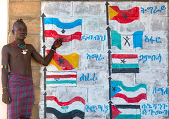 Hamer tribe teenager in a school in front of a painted wall with the regions flags of ethiopa, Omo valley, Turmi, Ethiopia (Eric Lafforgue) Tags: poverty africa school people color childhood horizontal painting outdoors photography necklace education mural day african tribal flags teenager bead omovalley schools ethiopia tribe development hamar oneperson developingcountry hamer hornofafrica ethiopian riftvalley wallpaintings eastafrica abyssinia realpeople teenageboy beadednecklace lookingatcamera ruralscene buildingexterior turmi africanethnicity 1people indigenousculture beadednecklaces oneteenageboyonly ethiopianethnicity ethio161857