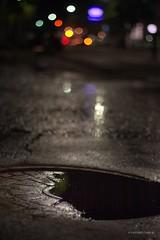 Siempre que llovi... (Tato C) Tags: street cars water rain night lights luces noche calle lluvia agua bokeh pavement drain tapa manhole autos humidity pavimento alcantarilla humedad
