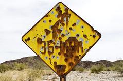 35 MPH Right Curve (Curtis Gregory Perry) Tags: california old mountain sign yellow photography photo nikon rust gun shot desert hole eagle schild mojave rusted bullet curve 35 letrero mph bord enseigne mohave   kyltti d300 wegweiser  teken indicacin liikennemerkki uithangbord  criteau