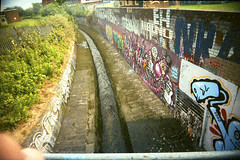 Meanwood Beck. (Saturated Imagery) Tags: film 35mm graffiti lomo xpro lomography crossprocessed saturated colours toycamera wideangle slidefilm uws expiredfilm 22mm meanwoodbeck vivitarultrawideandslim buslingthorpe epsonv500 agphotographic scotchchrome8003200