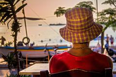 La dame au chapeau  carreaux (Lucille-bs) Tags: mer rouge europe lumire femme creta greece dos chapeau hania plage grce barque xania chania kriti crte khania lacane chapeaucarreaux