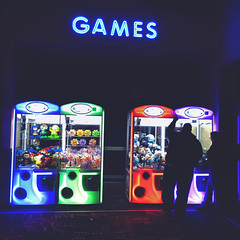 124 | 366 | V (Randomographer) Tags: light woman playing man game glass sign project dark movie fun toys big colorful theater neon cabinet crane arcade machine games human claw electricity difficult scam iphone 366 merchandiser