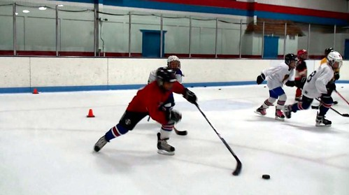 A hockey player playing keep away with the puck at a hockey clinic with Brad Perry