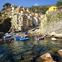 Picturesque harbor of Riomaggiore (Bn) Tags: world ocean park flowers blue trees houses sea summer vacation cactus sky orange sun sunlight moon holiday flower tower heritage classic water colors beautiful weather train buildings walking coast boat high topf50 warm mediterranean italia sailing ship torre gulf view hiking path five liguria shoreline hike case cliffs lovers quay historic unesco via national wharf terre sail botanic mountainside quaint incredible viewpoint picturesque coloured topf100 cinque adriatic riomaggiore italianriviera torri yellew dellamore 100faves 50faves guardiolas