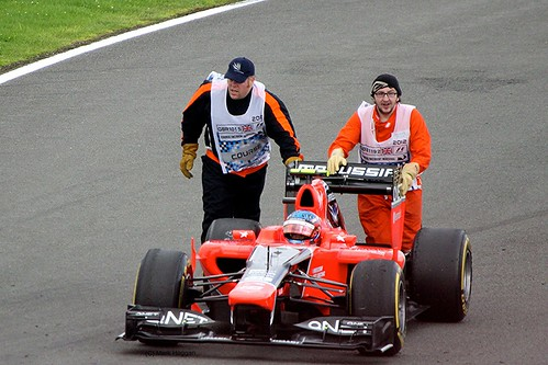 Charles Pic's Marussia pushed by Marshals at Silverstone