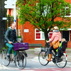 Street Scenes: Dutch families on the move (Peggy2012CREATIVELENZ) Tags: pink blue red white house tree green sunshine amsterdam spring purple candid tan bikes streetscene jeans riders peggy2012creativelenz wroughtironimg6721a