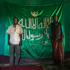 Sufi men worshippers in front of islamic flag, Harari region, Harar, Ethiopia (Eric Lafforgue) Tags: africa travel portrait people color men green square outdoors photography day african flag muslim islam faith religion indoor unescoworldheritagesite unesco indoors spirituality ethiopia adults sufi sufism 2people twopeople worshipper hornofafrica ethiopian harrar eastafrica placeofworship harar abyssinia arabiccalligraphy traditionalclothing lookingatcamera harari oromo harer harariregion hararjugol harergeprovince harergey ethio162923